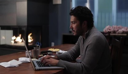 Hispanic man at home at table with laptop typing