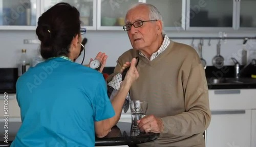 Caucasian nurse checking blood pressure of senior man