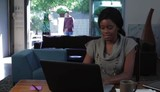 Black woman at home working on laptop as she is greeted by husband