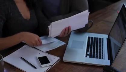 Couple at home sorting bills at laptop