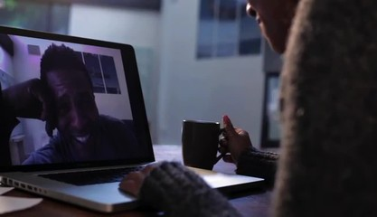 Black woman on laptop at home having a fun video conference with husband