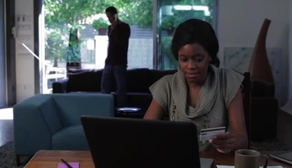Black woman using credit card at home working on laptop with partner in background on phone
