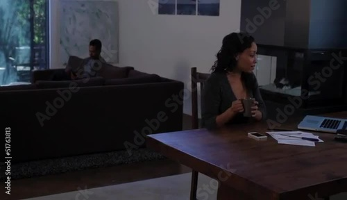 African American woman at home working with laptop with husband in background