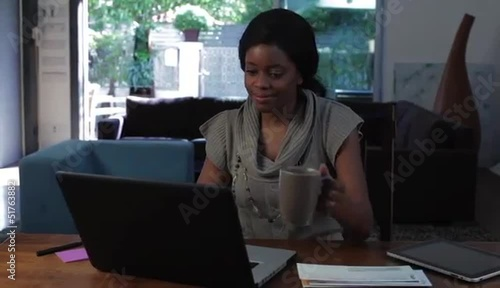 Black woman at home working on laptop