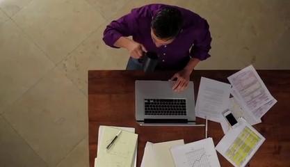 Hispanic man at table working on laptop