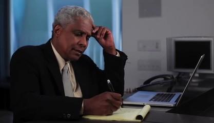 Senior businessman using laptop and making notes