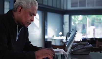 Senior man at home typing on laptop