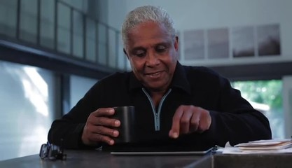 Senior man at home using digital tablet