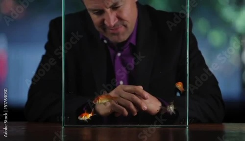 Hispanic man at table watching goldfish swim