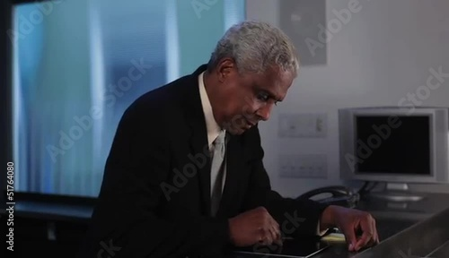 Arriving senior businessman using digital tablet and making cell phone