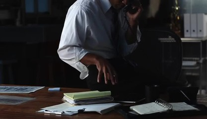 Businessman in the evening conversing on telephone and taking notes