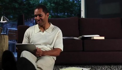 Mature man at home in evening working on digital tablet