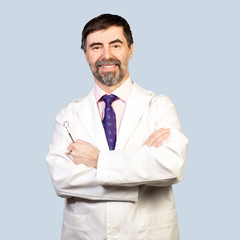Portrait of happy middle-aged dentist on a pale background