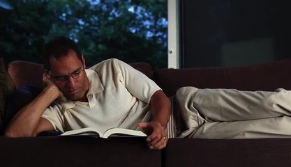 Mature man lying on sofa at home in evening reading a book