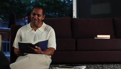 Mature man at home in evening reading a book