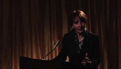 Businesswoman speaking at lectern to audience