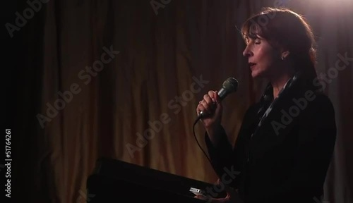 Businesswoman at lectern holding microphone, addressing audience and using cell phone