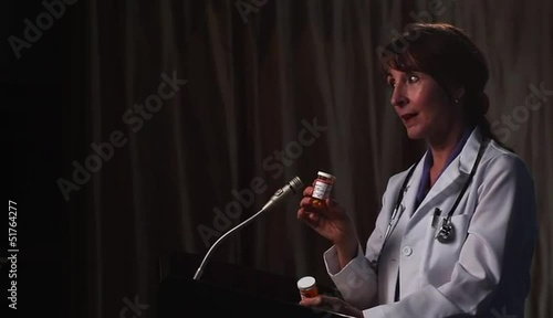 Doctor at lectern speaking while holding prescription bottles