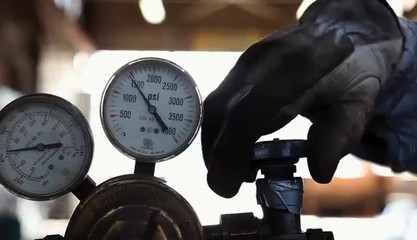 Worker turning on knob next gauges