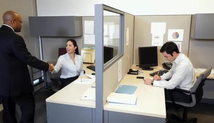 Businessman shaking hands with businesswoman in office cubicle