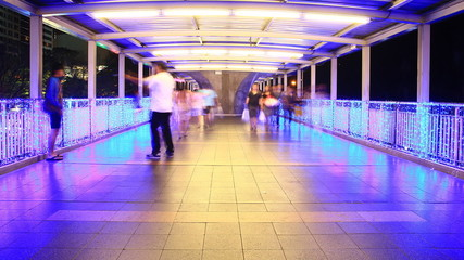 People walking on skywalk at night , time lapse