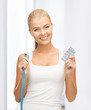 woman with measuring tape and diet pills