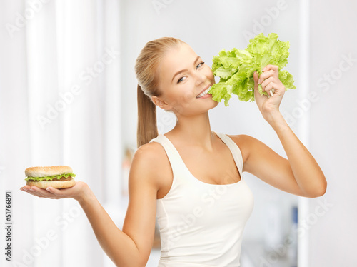 woman with green lettuce and hamburger