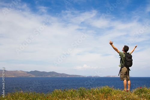 Young tourist with backpack enjoying sea view from top of a hill