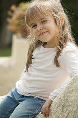 Smiling Little Girl Leaning to a Wall