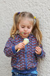 Cute little girl with blond hair and pigtails eating ice cream