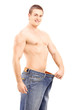Weight loss muscular man in a big pair of jeans