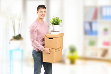 Young man carrying removal boxes in an apartment