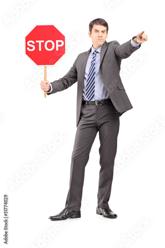 Full length portrait of a man in suit holding a stop sign