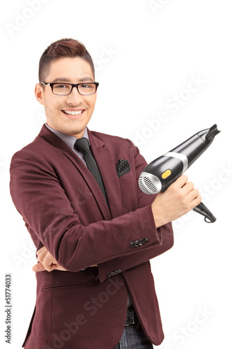 Smiling male hairdresser holding a blow dryer