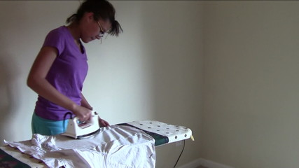 Young Woman ironing Blouse