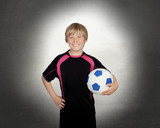 Preteen with a uniform for play soccer holding a ball