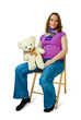 Young pregnant woman sitting on a chair with a toy
