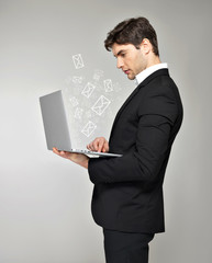 Business man with laptop and mail icon