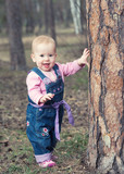 happy baby girl  stands on legs near a tree in the park outdoors
