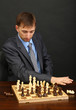 Young business man playing chess on black background