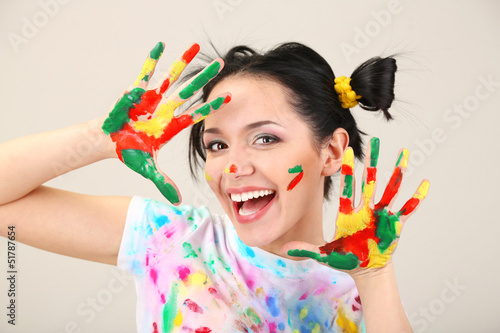 Young pretty painter with hands in paint, on gray background