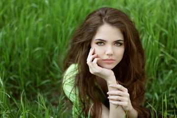 Young brunette woman on the green field grass, outdoors portrait