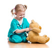 Adorable child with clothes of doctor playing with plush toy