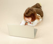 A little girl with a laptop lying on the floor