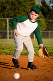 Young child fielding ball while playing baseball