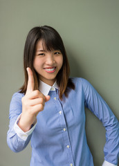 Asian office girl lifting her forefinger in grey background.