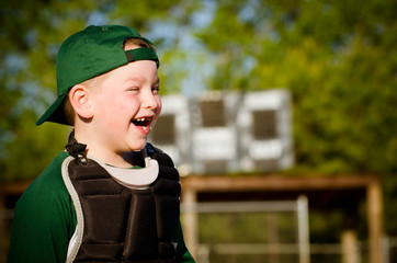 Portrait of child in catcher's gear laughing while playing
