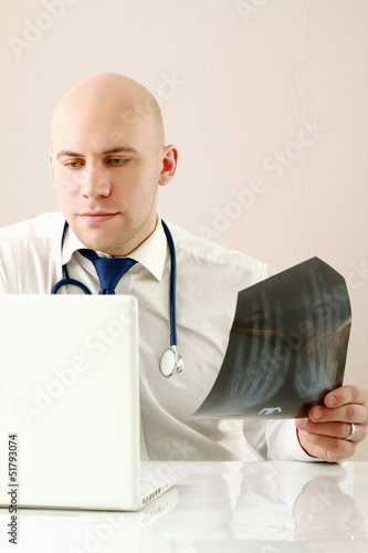A male doctor studying a x-ray image, sitting at the desk