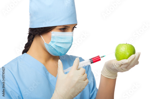 Chemist with syringe and apple