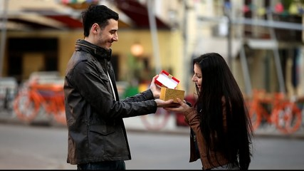 Couple with gift at city street